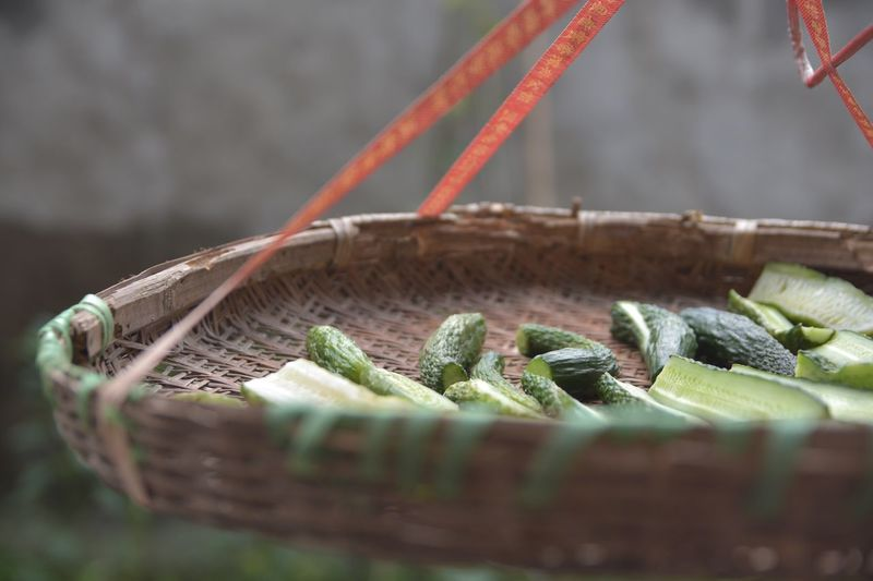 Close-Up Of Bitter Gourds In Wicker Basket