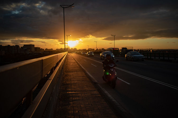 Sunset Transportation Sky Mode Of Transportation Land Vehicle Car Motor Vehicle Street Cloud - Sky City Architecture Street Light Road Nature Orange Color Built Structure The Way Forward Direction One Person Building Exterior Outdoors