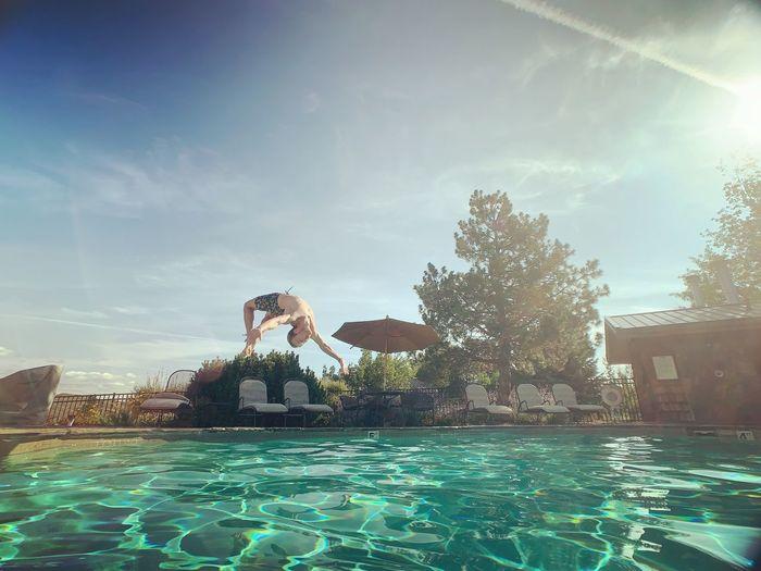 Man swimming in pool against sky