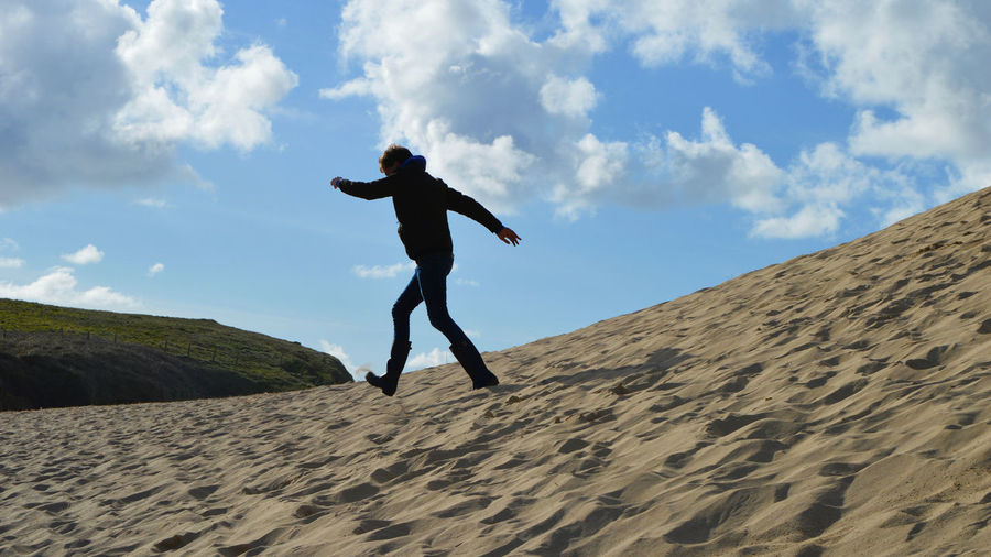 Low angle view of man jumping on sand