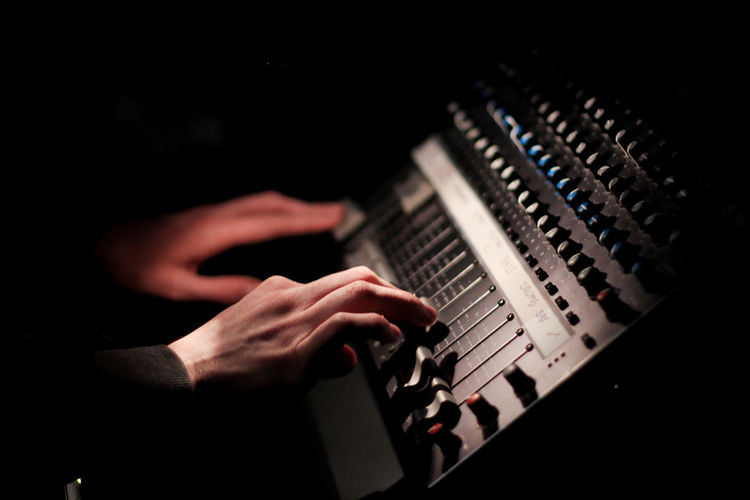 Cropped Hands Of Musician Using Sound Mixer In Dark At Recording Studio