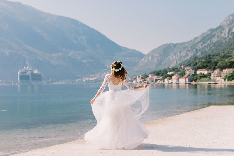 Rear view of bride standing at beach against mountains and sky