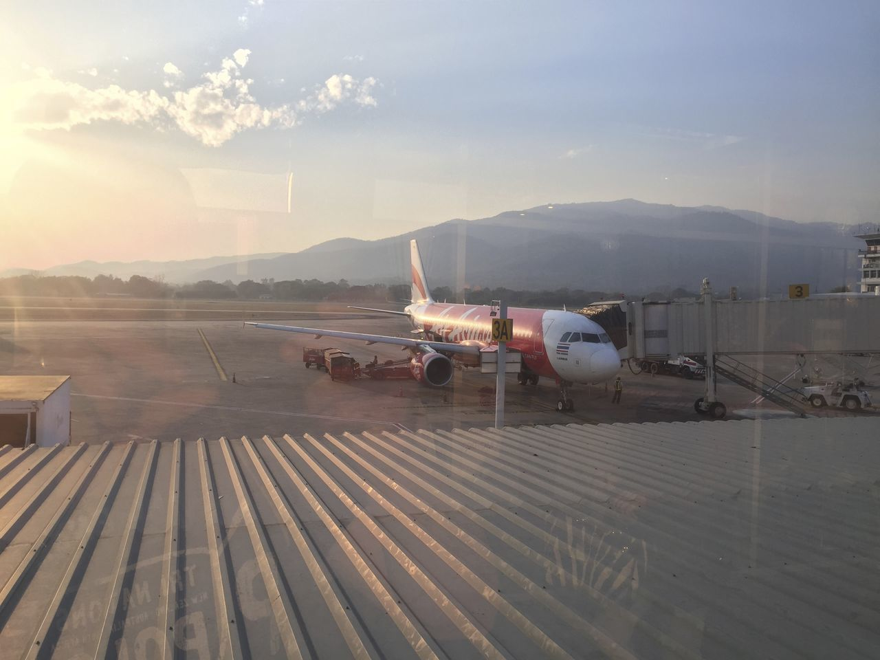 airplane, airport, air vehicle, transportation, airport runway, mode of transport, runway, sky, outdoors, commercial airplane, mountain, sunset, day, no people, airport departure area, flying, nature, airplane wing