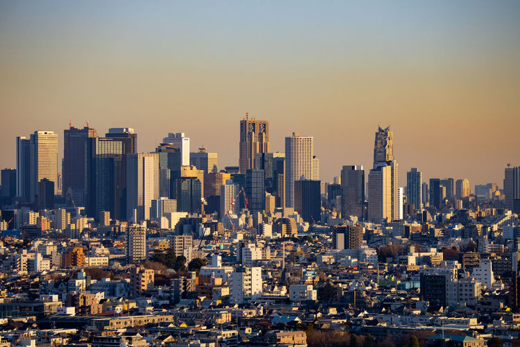 Modern buildings in shinjuku city against sky during sunset