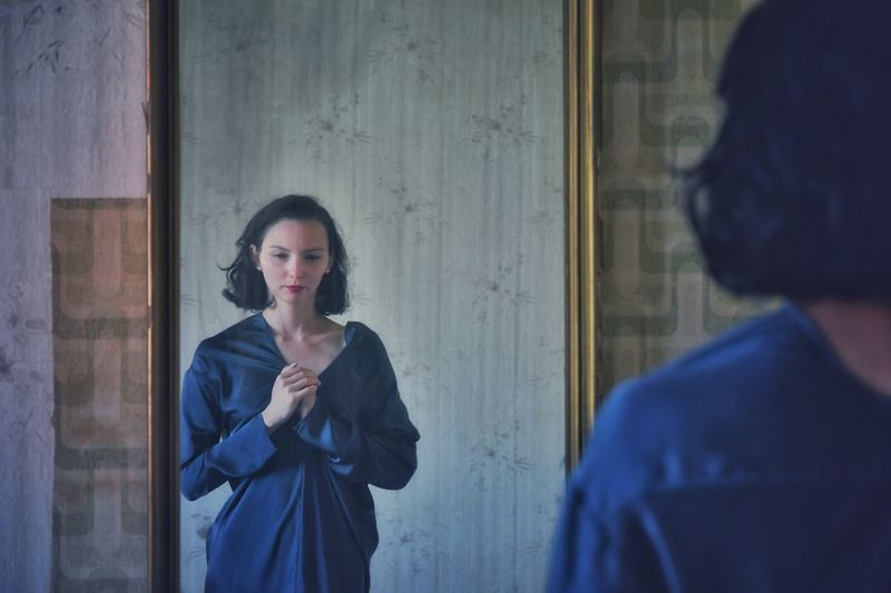 Thoughtful woman standing by mirror at home