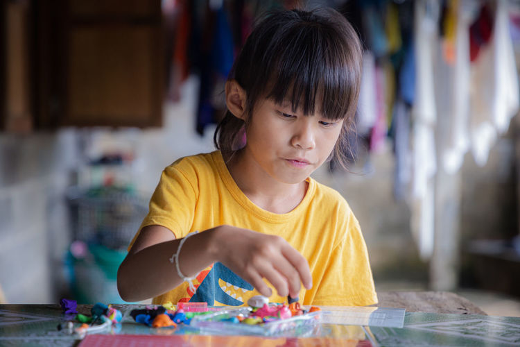 Cute girl playing with clay at home