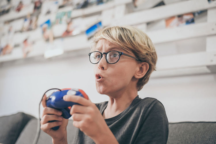 Boy playing video game while sitting on sofa in living room at home