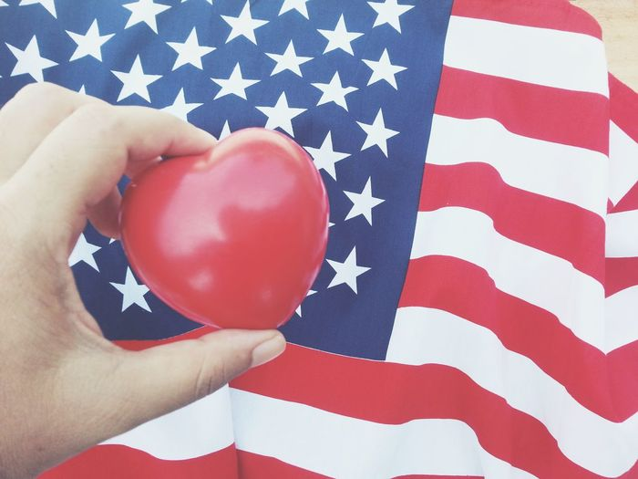 Close up hand holding red heart with american flag background Memorial Day Remember USA Country America Greeting Celebrate 4th Of July Celebration Event Nation Flag Independence Soldier Holiday Patriotism Anniversary Liberty Memorial Pride Army Peace Memory Peaceful Cheerful
