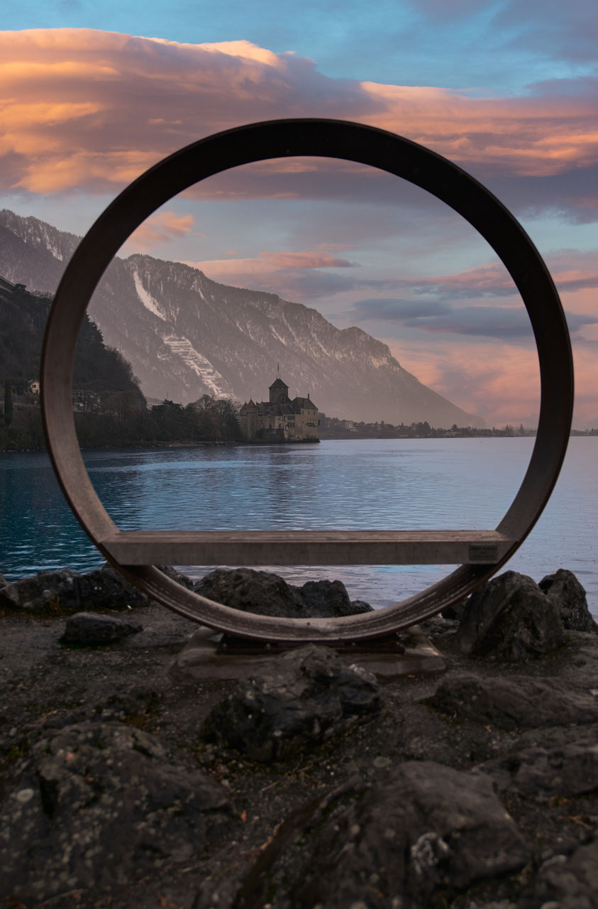SCENIC VIEW OF SEA AGAINST SKY DURING SUNSET SEEN THROUGH ARCH