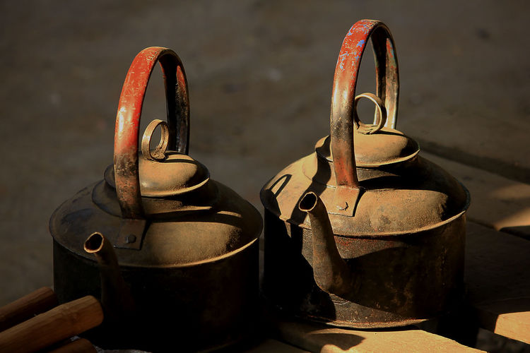 Close-up of old kettles on table