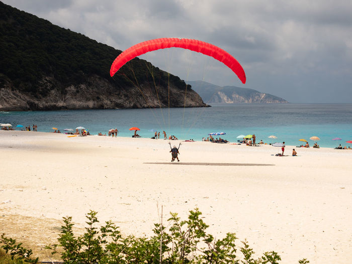 Land Nature Paragliding Red Adventure Beach Beauty In Nature Extreme Sports Flying Horizon Over Water Leisure Activity Lifestyles Outdoors Parachute Real People Sand Sea Sky Sport Unrecognizable Person Water