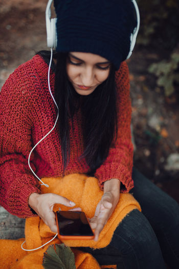 High angle view of young woman wearing sweater listening music sitting in forest