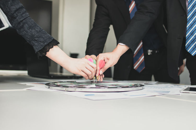 Colleagues holding dart on bull-eye at table in office