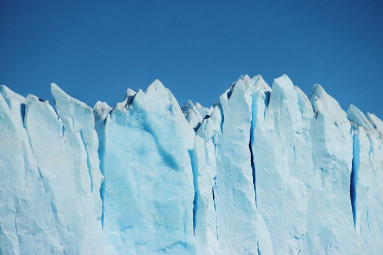 Low angle view of glacier against clear blue sky