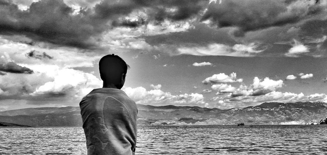 Rear View Of Boy Wrapped In Towel Looking At Sea And Mountains At Krk Island