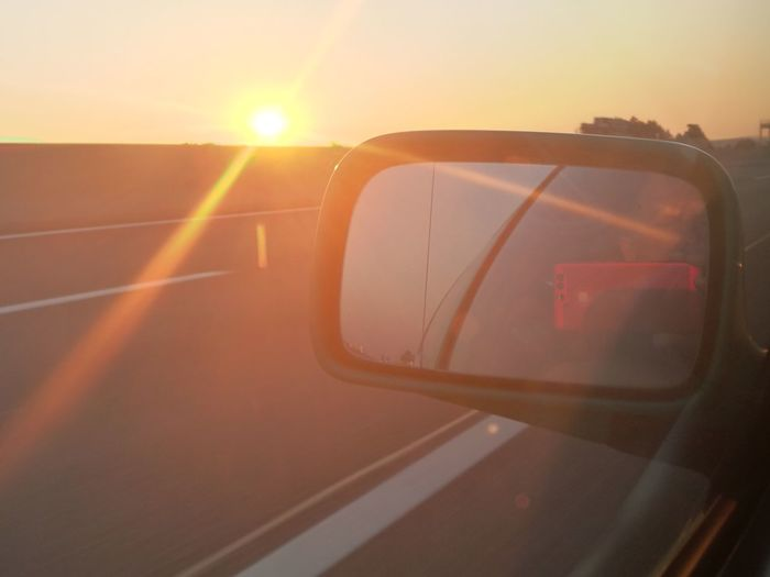 Reflection of sky on side-view mirror at sunset