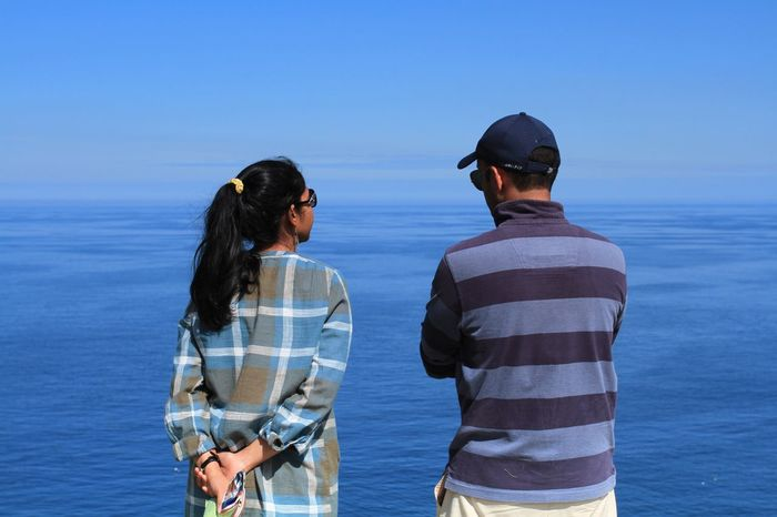 A modern, Asian couple on a sightseeing holiday at Tintagel in Cornwall, UK standing on the edge of a cliff top overlooking a deep, blue ocean whilst deep in conversation. Two People Real People Sea Standing Day Water Sky Outdoors Togetherness Lifestyles People Cornwall Tintagel Couple Asian  Vacations Conversation Conversations Man And Woman Husband And Wife Friendship Sea View Ocean Ocean View Talking Connected By Travel