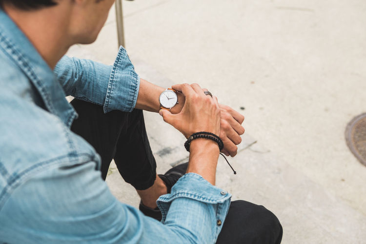 Young Man casually dressed wearing analog watch in the Urban environment Holding Real People Men Casual Clothing One Person Midsection High Angle View Jeans Lifestyles Hand Sitting Day Technology Adult Human Hand Human Body Part Focus On Foreground Denim Leisure Activity Watch Wrist Watch Jewellery Jewelry Young Adult Young Men City City Life Urban Street
