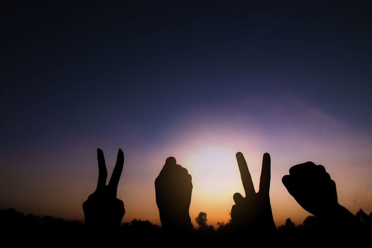 Silhouette of hands gesture v sign and fist power for victory/peace. success and winner in 2020.