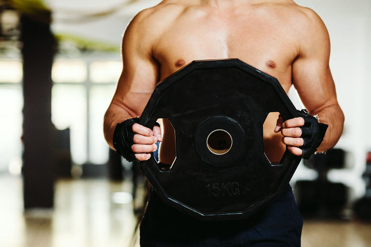 Midsection Of Shirtless Man Exercising In Gym