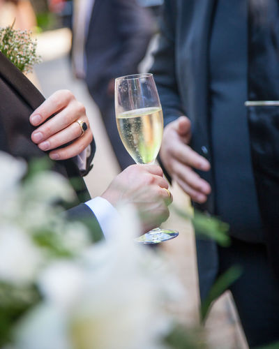 Midsection of man holding champagne