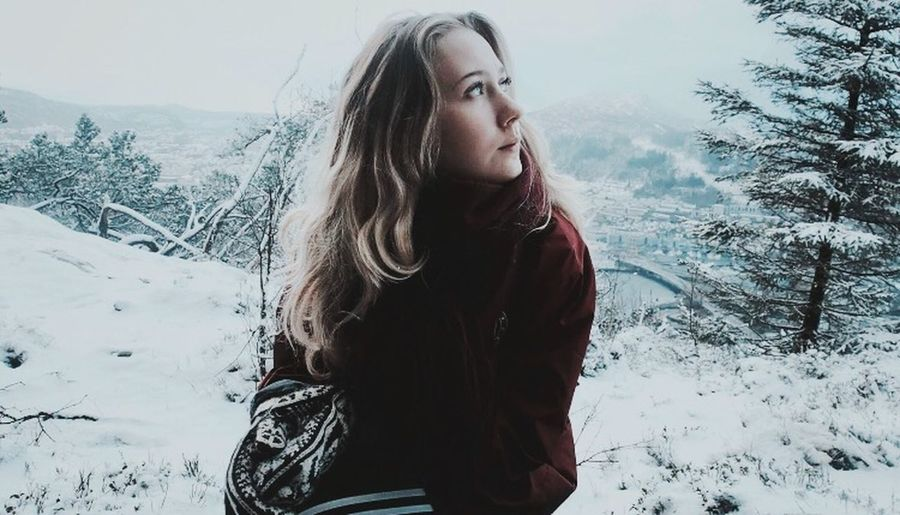 Beautiful young woman on snow covered land