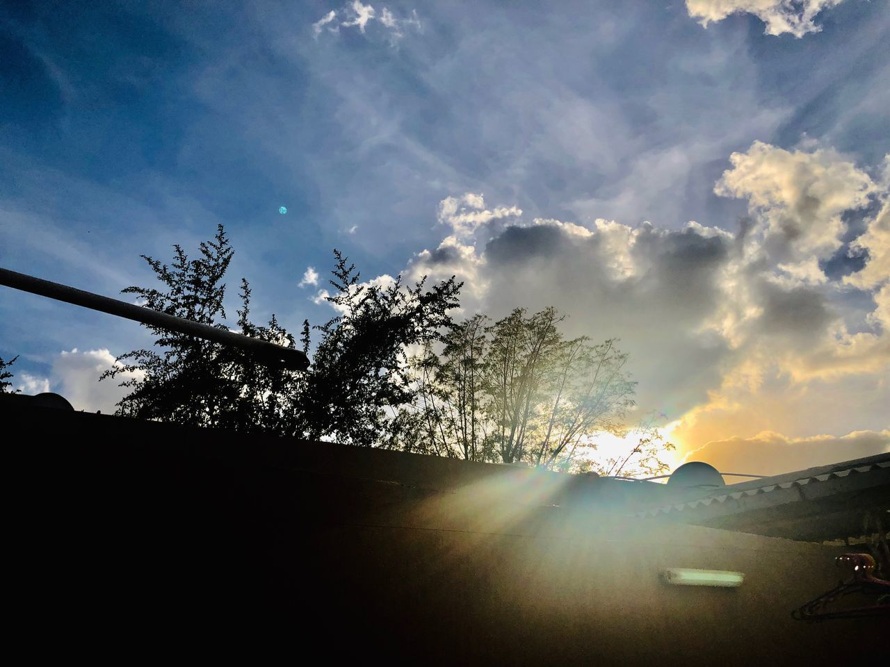 sky, cloud - sky, tree, sunlight, plant, nature, sun, lens flare, sunbeam, silhouette, car, motor vehicle, no people, mode of transportation, transportation, sunset, low angle view, beauty in nature, architecture, built structure, outdoors, bright, solar flare