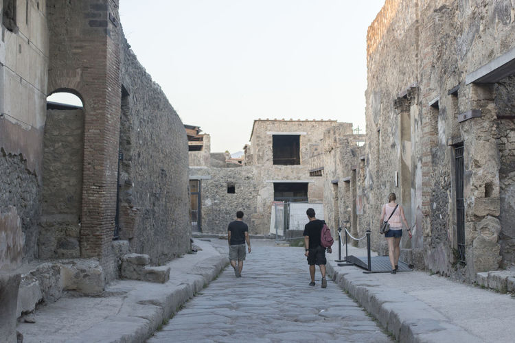 Rear view of people walking in front of historic building