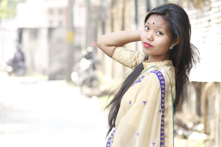 Portrait Of Young Woman In Sari Standing On Street