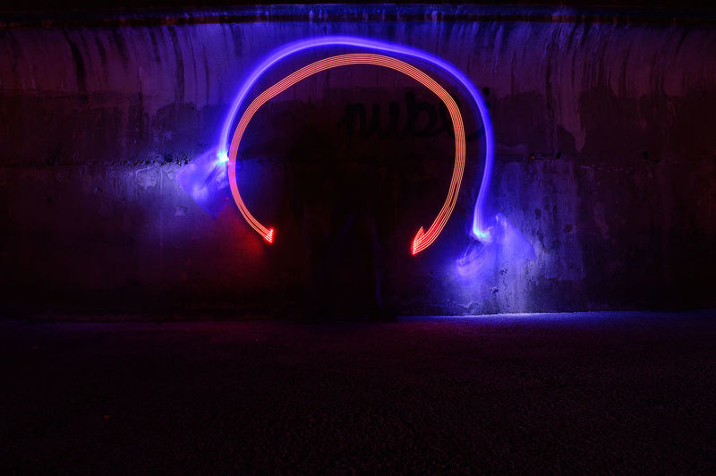 Silhouette man standing in illuminated tunnel