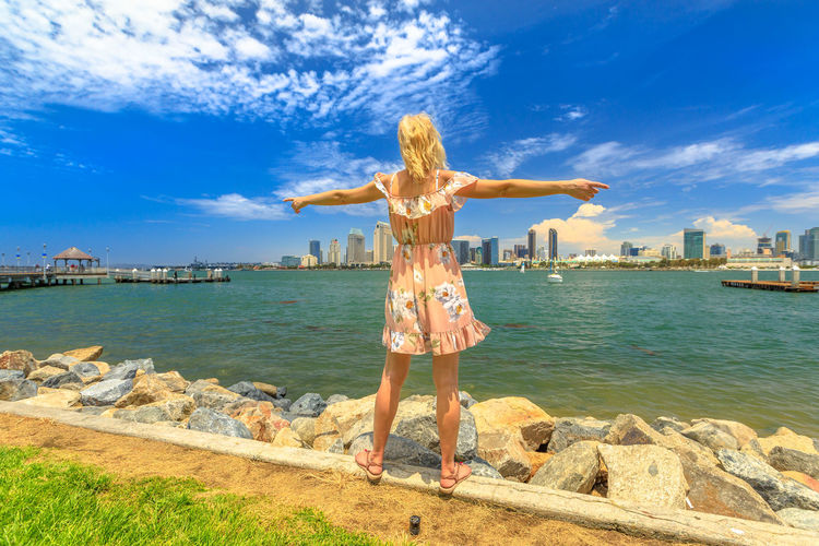 Blonde lady enjoying at San Diego Downtown skyline with skyscrapers in California, USA from Coronado Island. Tourist woman in summer american holidays. Waterfront and urban cityscape in San Diego Bay. United States America American Woman People Female Girl California San Diego San Diego, California Beach Sea Seascape Skyline Cityscape Shore Nature Vacations Holiday Summer Lifestyles Tourist Coronado Coronado Beach Coronado Island Water Sky Cloud - Sky Arms Outstretched Full Length Day One Person Architecture Built Structure Leisure Activity Human Arm Real People Limb Standing Building Exterior Casual Clothing Outdoors Hairstyle