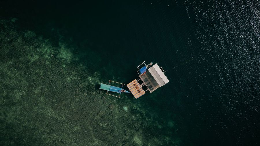 Aerial view of built structure and boat floating on sea