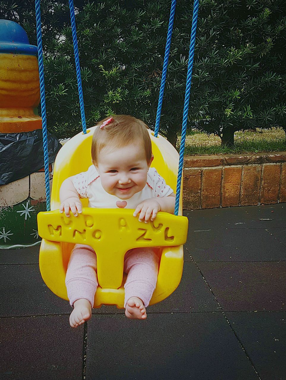 childhood, playground, swing, outdoor play equipment, sitting, one person, leisure activity, real people, happiness, playing, smiling, full length, fun, park - man made space, enjoyment, day, lifestyles, cheerful, outdoors, people