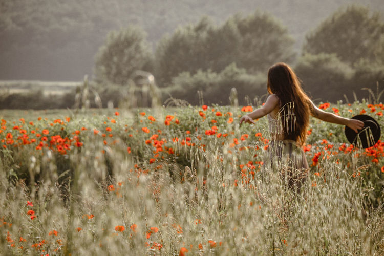 Woman amidst flowering plants on field
