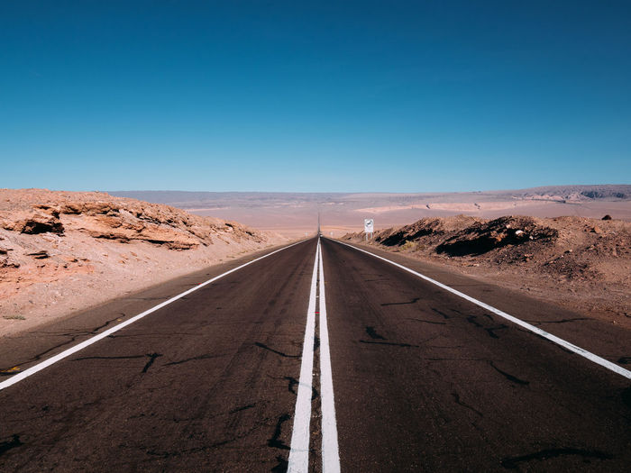 Sky Road Direction The Way Forward Transportation Desert Diminishing Perspective Scenics - Nature vanishing point Clear Sky Sign Landscape Road Marking Nature Arid Climate Climate Blue Symbol Marking Environment No People Outdoors Straight