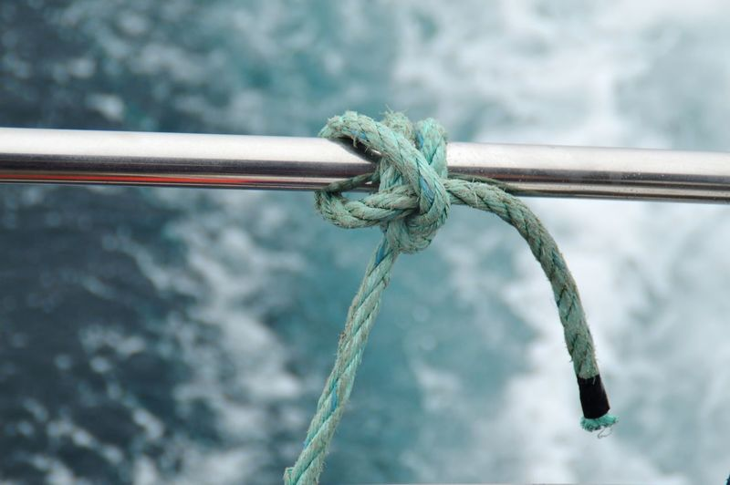 Close-up of rope tied on metal rail on boat