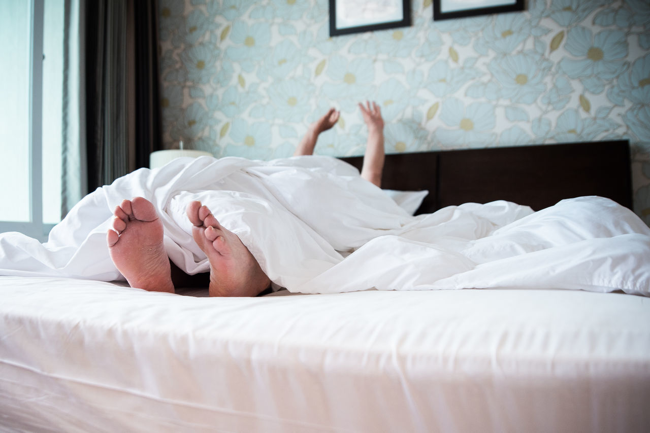 Person relaxing under blanket on bed at home