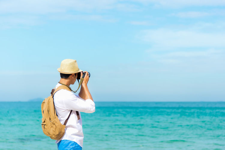 Woman photographing sea against sky
