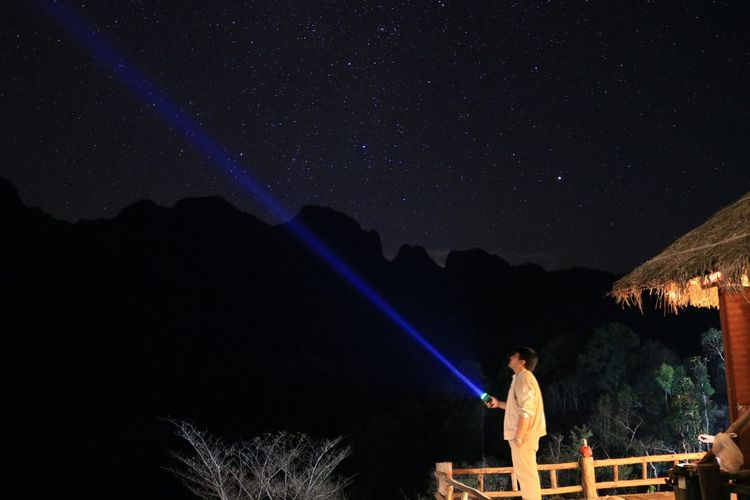 Man Holding Flashlight Against Star Field
