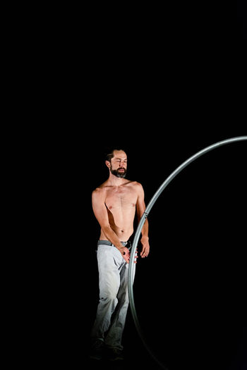 Circus Adult Black Background Chest Copy Space Front View Full Length Holding Indoors  Males  Men Mid Adult Muscular Build One Person Shirtless Shorts Standing Strength Studio Shot Three Quarter Length Young Adult