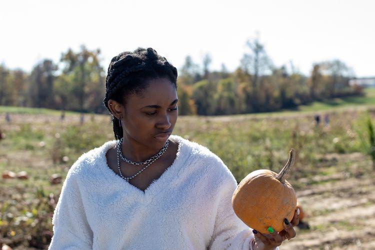 Teenage girl holding pumpkin on field