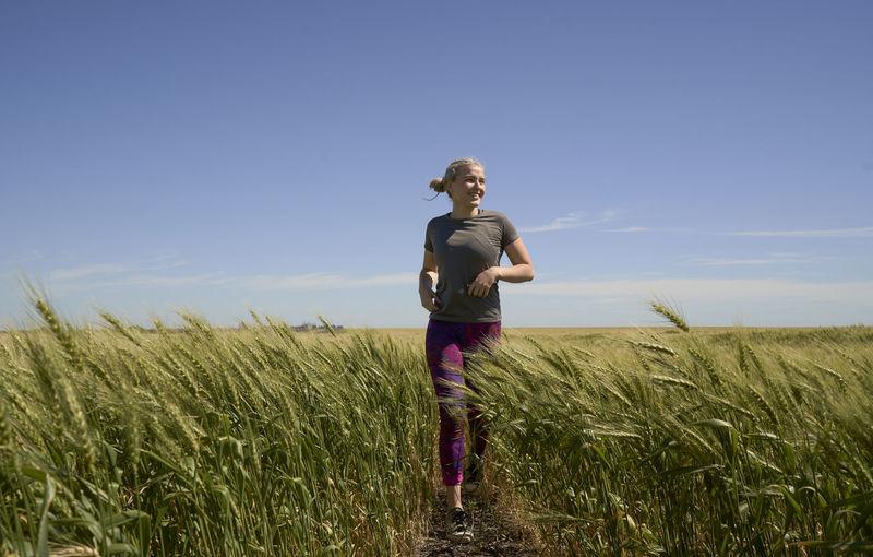 Young european latin woman running in wheat field