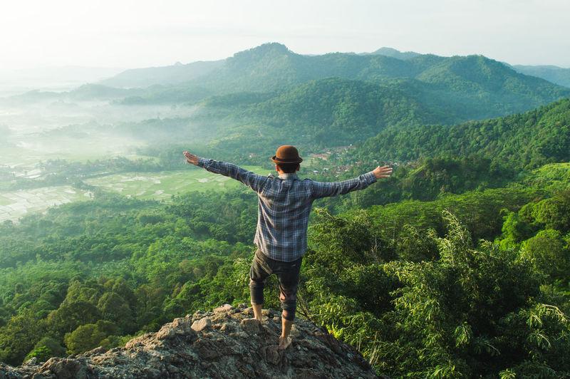 Man standing on cliff against landscape