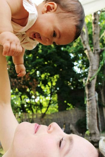 Close-Up Of Mother Lifting Cheerful Daughter At Park