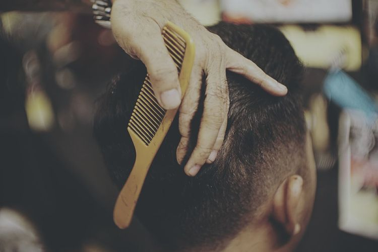 Cropped hand of barber cutting man hair at salon