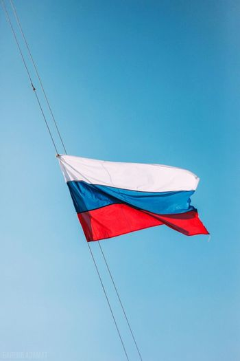 Low angle view of russian flag waving against clear blue sky