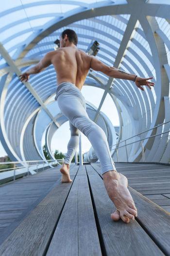 Low angle view of shirtless man dancing on bridge