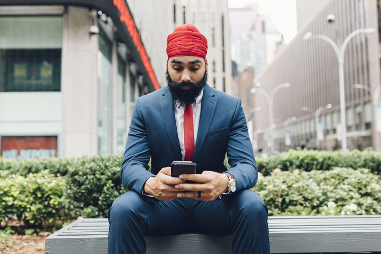Full length of young man using mobile phone