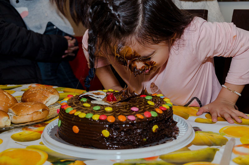Girl with cake on face during birthday party