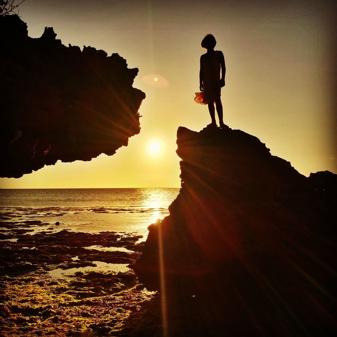sunset, silhouette, full length, rock - object, sea, real people, standing, nature, adventure, leisure activity, one person, sky, men, cliff, scenics, outdoors, lifestyles, beach, beauty in nature, women, water, horizon over water, day, people